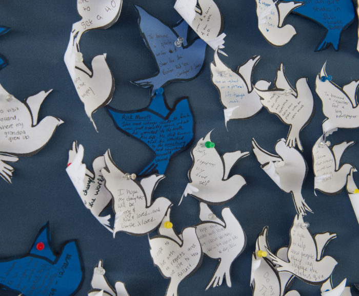 Paper peace doves cut out and pasted on a board.