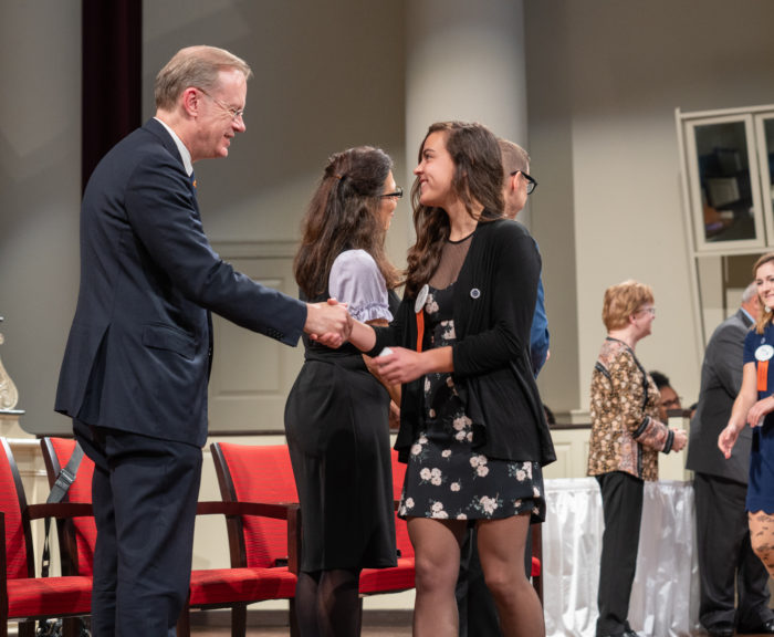 Bethany Murphy shaking hands with Chancellor Syverud at Remembrance Convocation